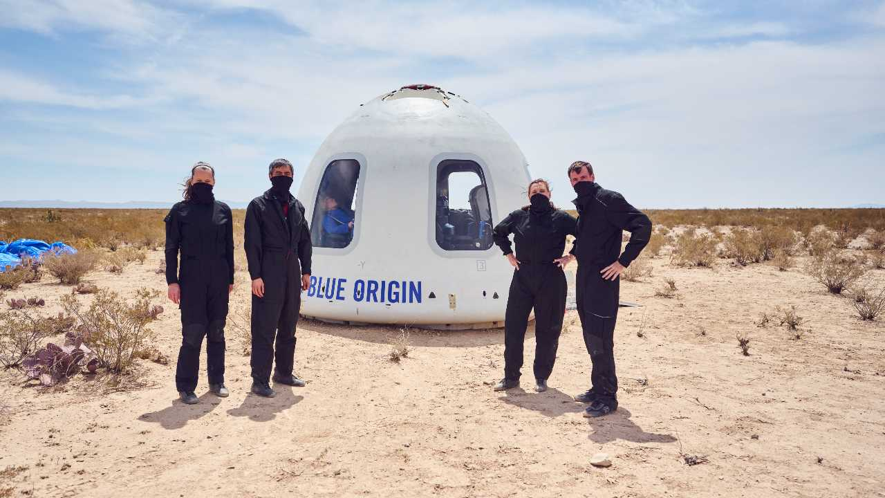 Blue Origin personnel standing in as astronauts during Mission NS-15 pose in front of the New Shepard Crew Capsule after a successful mission. (April 14, 2021) Image credit: Blue Origin