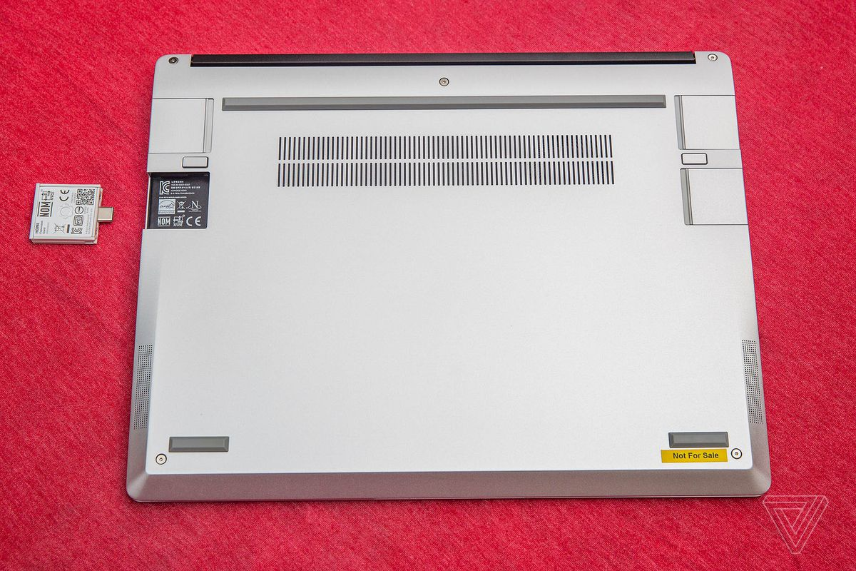 The Framework laptop was closed upside down with a red tablecloth.  One of its four port slots is empty.  The expansion card sits next to an empty gate upside down with its QR code facing up.